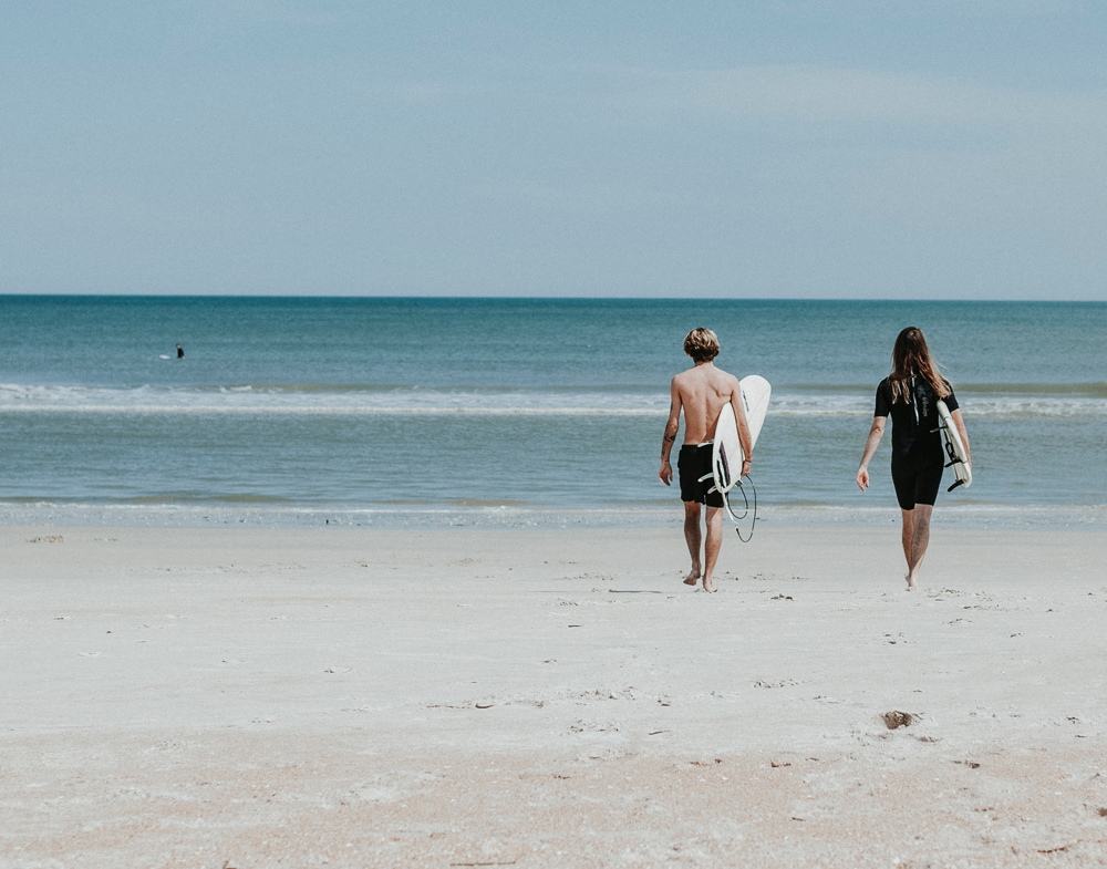 image showing two young adults with surfboards